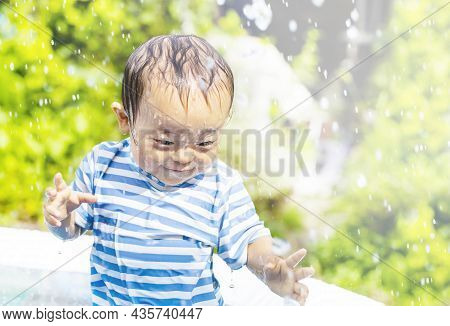 Baby Boy Plays A Home Pool Happily Outdoors On A Hot Day Of The Midsummer. The Pretty Boy Of The Smi
