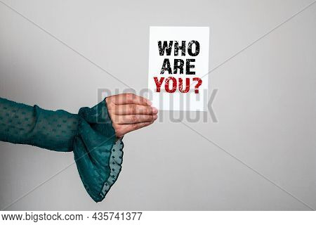 Who Are You. Note Paper With A Question In A Womans Hands