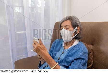 Covid-19 Pandemic, Elderly Asian Woman Relax On Couch In Living Room Browsing Wireless Internet On C