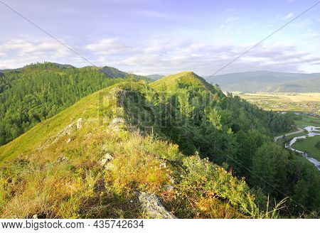 The Top Of The Mountains In The Morning Light Under A Blue Cloudy Sky In The Altai Mountains. Siberi
