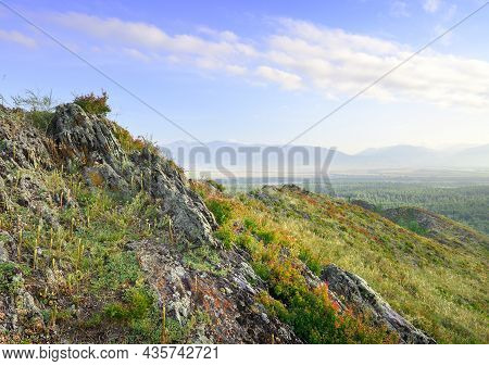 Sharp Rocks On The Top Of A Mountain Above A Mountain Valley Under A Blue Cloudy Sky. Siberia, Russi