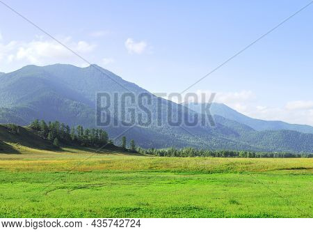 A Green Meadow At The Foot Of The Mountains Under A Blue Cloudy Sky. Siberia, Russia