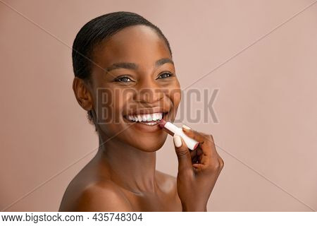 Cheerful beautiful woman applying natural lip balm brown background with copy space. Portrait of black woman applying lipstick while smiling. African american lady applying balm to her lips isolated.