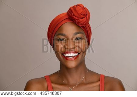 Portrait of beautiful african woman with red headscarf against brown background with copy space. Cheerful black mid woman wearing ethnicity headband. Mature happy lady with traditional clothes.