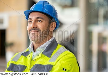 Mature engineer at construction site with safety vest and helmet looking away. Confident architect standing at site dreaming about finished project. Mature bricklayer thinking and day dreaming.