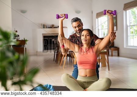 Middle aged man helping ethnic woman working with dumbbells at home. Black fit woman with her personal fitness trainer exercising with weights. Multiethnic girl doing chest and shoulder dumbbell press