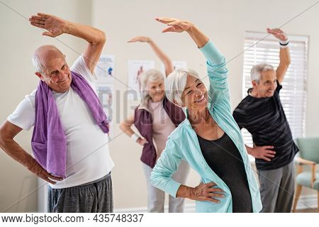 Group of seniors doing stretching exercise together at retirement centre. Elderly men and old women exercising at nursing home during daily fitness. Retired couples exercising at care facility.