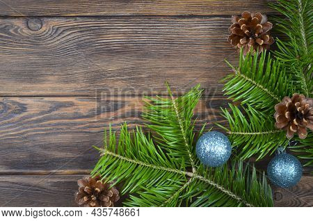 Christmas Background Or Frame For Congratulations Or Text, Spruce Branches With Cones On A Wooden Ba