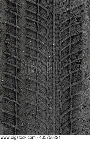 Traces Of Car Tire Tread In The Ground. Pattern. Dark Abstract Background. Imprint Of Wheels. Textur