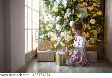 Little Girl In Beautiful Dress Is Sitting Under Christmas Tree With Gift Box And Bow. Light From A L