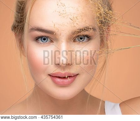 Closeup portrait of young beautiful woman with a healthy  skin of the face. Blonde girl with a bunch spring dry field flowers near the face - over colored background. Beauty face care concept.