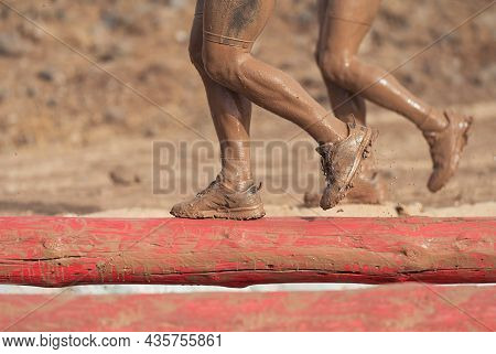 Mud Race Runners. Participants Walking On The Tree Trunk, Catches Balance Above The Pit Full Of Wate