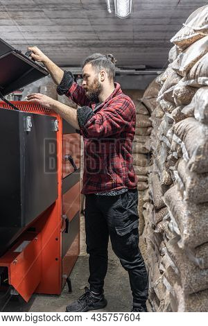 The Young Man Looking Into A Solid Fuel Boiler, Working With Biofuels, Economical Heating.