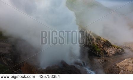 A Column Of Thick Steam Rises From The Cauldron Of An Erupting Geyser, Splashes Of Boiling Water Sca