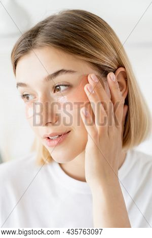 Facial Care. Skin Cosmetology. Morning Routine. Gentle Young Woman Touching Collagen Eye Patches On
