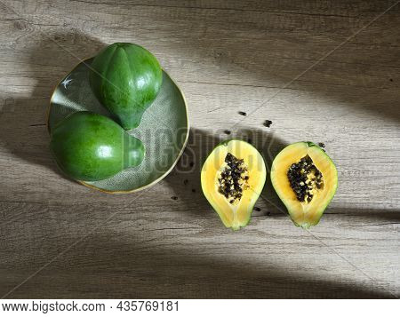 Two Whole And Two Halves Green Papayas On Wooden Surface