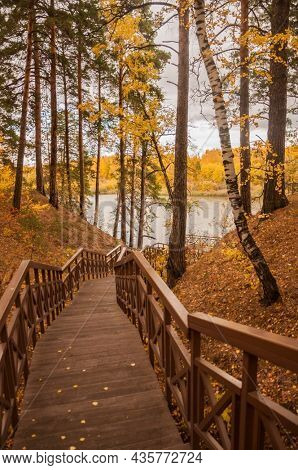 Old wooden bridge with stairs in autumn forest. Staircase in the wood. Footbridge in park. Adventure and explore concept