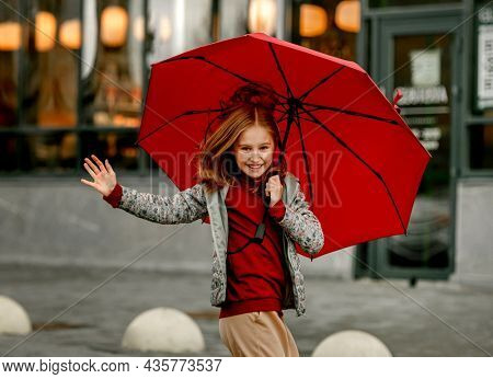 Preteen girl wearing roober boots and holding umbrella jumping in rainy autumn day and smiling. Pretty child in gumboots having fun at wet street