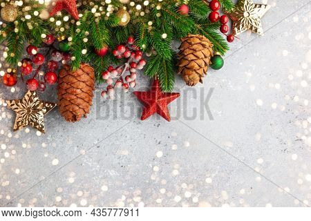 Christmas or New Year background with green fir branches, red berries, Christmas ornaments and cones. Winter holiday concept, top view, copy space