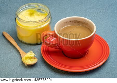 cup of fresh fatty coffee with ghee (clarified butter) and MCT oil - ketogenic diet concept