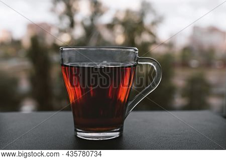 A Cup Of Hot Tea Stands By The Window On A Cold Autumn Day