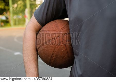 Basketball Ball In The Hand Of A Man On The Outdoor Sports Ground