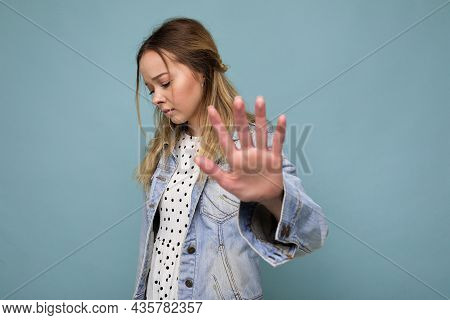 Shot Of Young Sad Upset Attractive Blonde Woman With Sincere Emotions Wearing Jean Jacket Isolated O