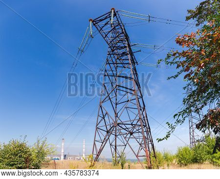 Steel Lattice Anchor Transmission Tower Of Overhead Power Line Against The Sky And Distant Thermal P