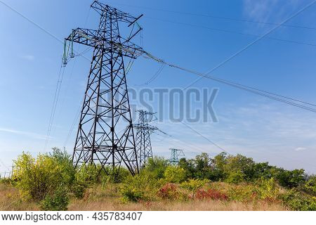 Steel Lattice Anchor Transmission Towers Of Overhead Power Lines Installed On Hill Over The Shrubs A