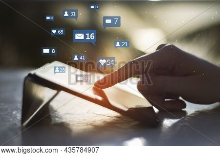 Close Up Of Hand Using Tablet Device At Desktop With Social Media Icons On Blurry Outdoor Background
