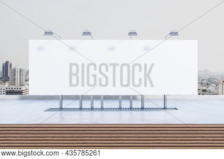 Empty White Billboard Poster On Rooftop With City In Daylight In The Background. Outdoor Advertiseme