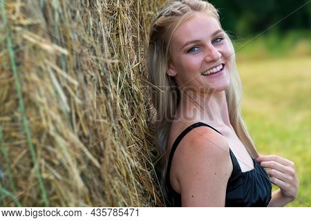 A gorgeous blonde farmers daughter poses outdoors in an farm environment