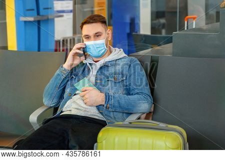 Attractive Young Man In Medical Face Mask Talking Using Smartphone In Airport Lounge With Suitcase H