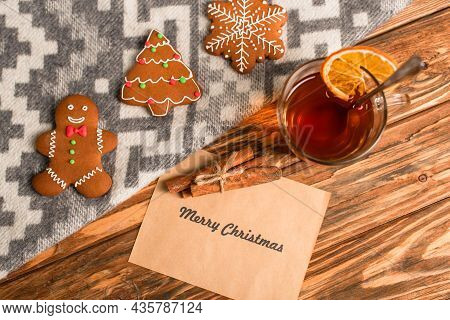 Top View Of Gingerbread Cookies On Blanket Near Greeting Card With Merry Christmas Lettering And Cup