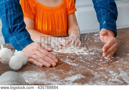 Little Girl Cooking Food In Kitchen With Dad. Daddys Hands Help Childrens Hands To Knead Dough. Chil