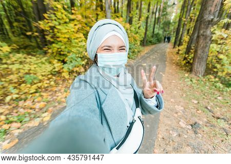Muslim Girl In A Medical Mask Makes A Selfie. Portrait Of Islamic Arabian Woman In Park During A Pan