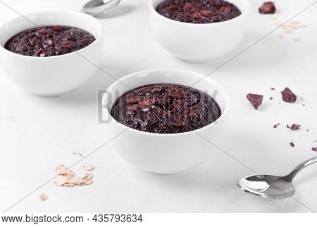 Baked Oats With Chocolate And Cocoa In Portion Cup On The White Table. Porridge Variation For Breakf