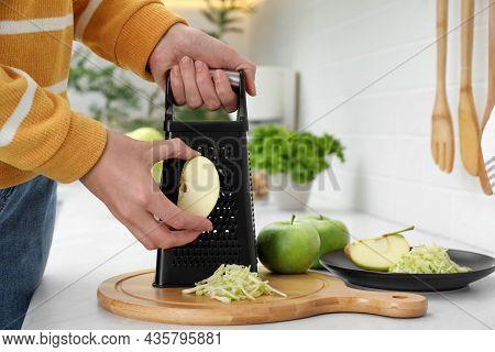 Woman Grating Fresh Green Apple At Kitchen Counter, Closeup