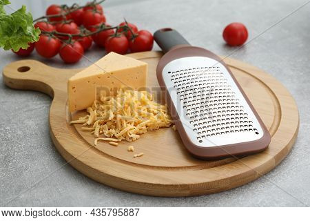 Wooden Board With Grater, Cheese And Vegetables On Grey Table