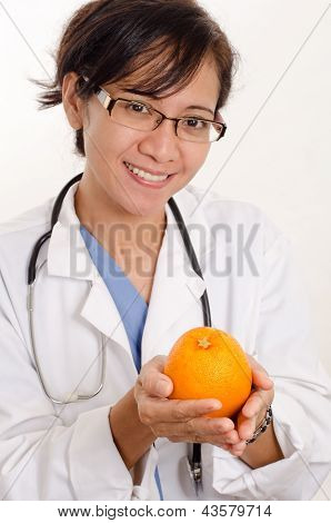 Attractive Filipino Asian Nurse Doctor Holding Orange