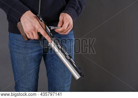Gun Shooting Sport. Man Holding Standard Pistol On Dark Background, Closeup. Space For Text