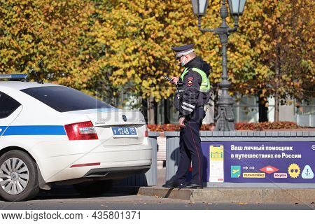 Moscow, Russia - October 2021: Traffic Police Officer In Mask Standing On The Road With Smartphone N