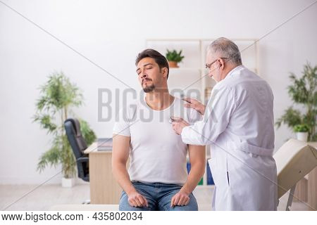 Young male patient visiting old male doctor