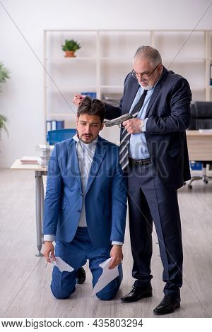 Old boss and young male employee in bullying concept
