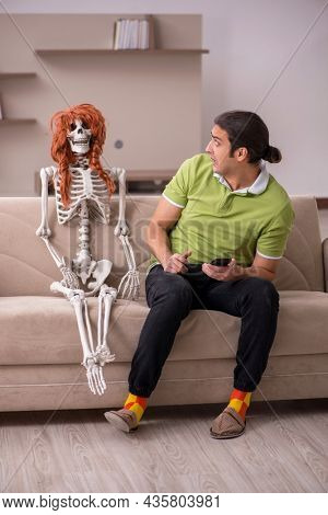 Young man sitting on the sofa with female skeleton