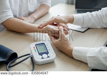 The Man Doctor Measures The Wrist Pulse, The Heartbeat Of The Patient, And Discusses Health Care Clo