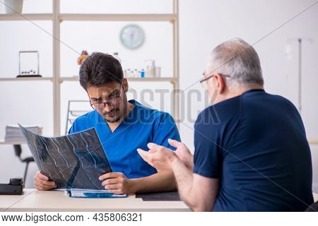 Old man visiting young male doctor radiologist