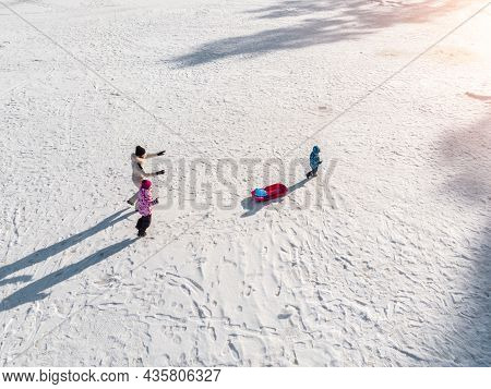 Aerial Top View Young Adult Mother Wear Jacket Enjoy Fun Sledging Two Cute Little Sibling Kids Boy G