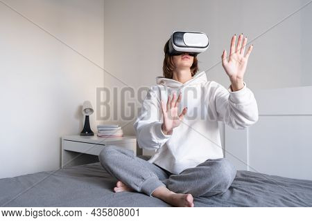 The Girl Looks Into Virtual Reality Glasses At Home. A Young Woman Plays Virtual Games Through A Spe