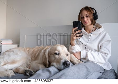 Cute Girl Listens To Music With A Dog On The Bed. A Young Woman In The Bedroom Sits On The Phone And